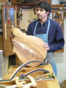 Jim Worland, custom acoustic guitar builder, holding a harp guitar that he's working on.