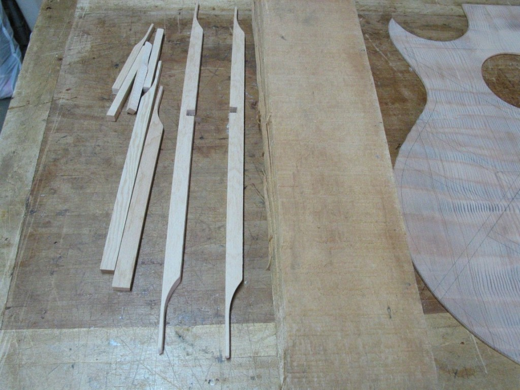 I start with a slab of sitka spruce and cut it into thin pieces, then shape the pieces to make the bracing wood for the top. These will be glued to the underside of the top to reinforce it.